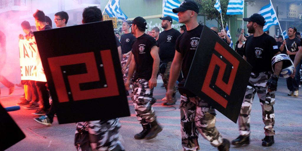 ATHENS, GREECE - MAY 26: Members of the extreme-right Golden Dawn party hold shields with their party symbol on as they guard party supporters during a gathering on May 26, 2013 in Athens, Greece. The far right movement, Golden Dawn, have seen their popularity increase on the back of the crippling austerity measures taking place in Greece at the moment. Whilst many of their policies and ideologies are condemned by the wider public Golden Dawn's support appears to be growing thanks to their Greece belongs to Greeks ethos. (Photo by Milos Bicanski/Getty Images)